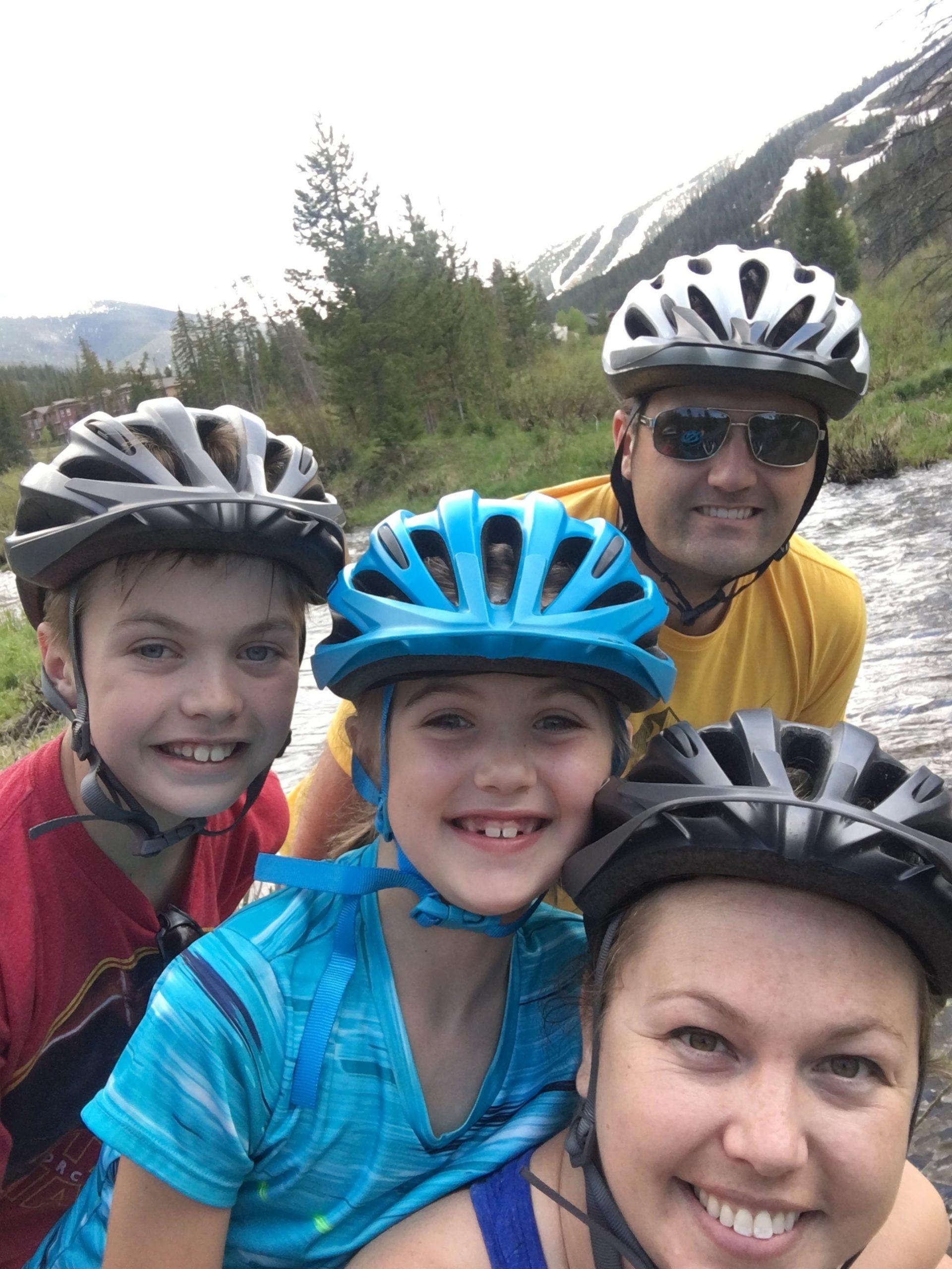 Family of four wearing biking helmets.